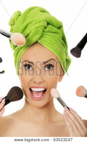 Beautiful shocked woman has brushes around face.