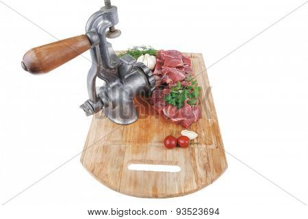 fresh uncooked beef meat slices over wooden cutting board ready to prepare with green hot and red peppers and grinder isolated over white background