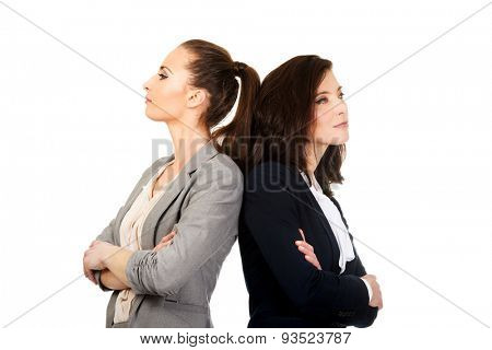 Two offended businesswomen leaning on each other.
