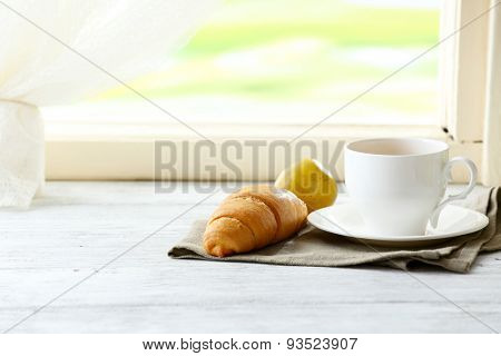 Tasty croissant and cup of tea on napkin on light background