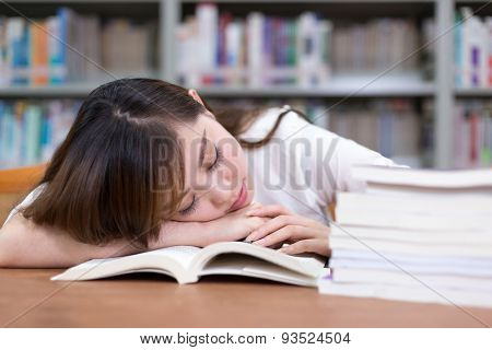 Beautiful asian female student take nap in library during studying stack of books.