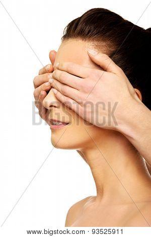 Beautiful woman covering friend's eyes.