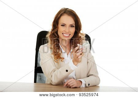 Business woman by a desk holding a toy plane.