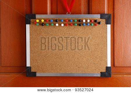 Cork board with colorful push pins hanging by a door