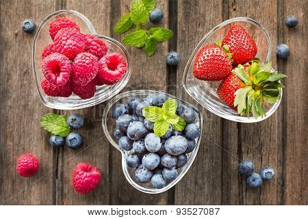 Mix Of Fresh Berries In Three  Glass Ramekins In Shape Of Heart, On Wooden Background, Top View, Hor
