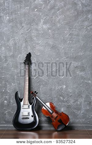Electric guitar and violin on gray wall background