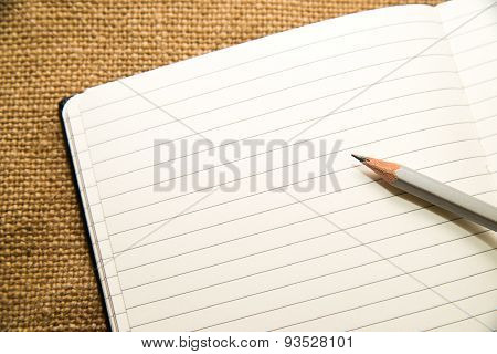 Opened Notebook And Pencil On The Old Tissue