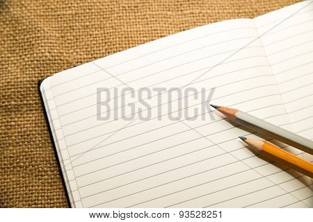 Opened Notebook And Pencils On The Old Tissue