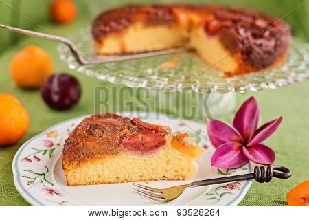 Slice Of Homemade Upside-down Plum Cake On Plate With Fork And Purple Frangipani Flower