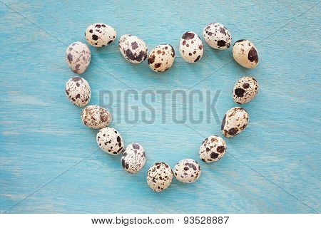 Quail Eggs On A Blue Wooden Background In Shape Of Heart , Top View