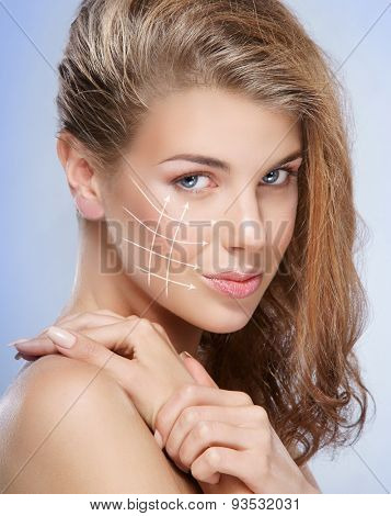 Spa portrait of a young and healthy woman with arrows on her face. Plastic surgery concept.