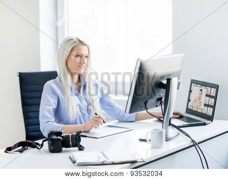 Young, attractive and confident woman working in office. Retoucher editing photos.