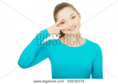 Happy smiling teenager with victory sign on eye.