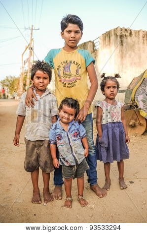 HAMPI, INDIA - 31 JANUARY 2015: Three young Indian boys and little girl standing in dusty street.