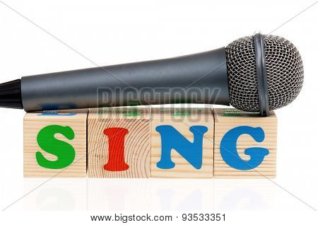 Sing word formed by wood alphabet blocks with microphone on white background