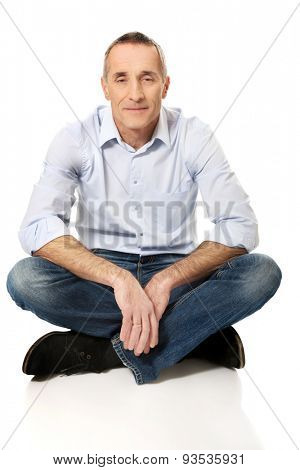 Mature man sitting cross-legged on the floor.