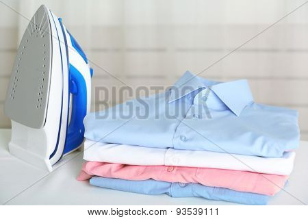 Pile of clothes and electric iron on fabric background
