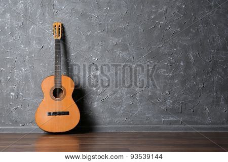 Classical acoustic guitar on gray wall background