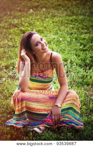 smiling young woman in long colorful dress sit on grass enjoy in warm summer day on meadow