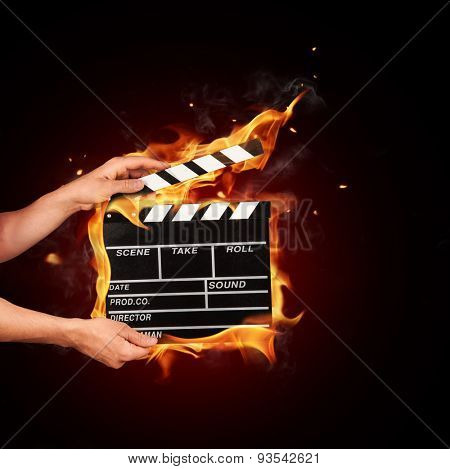 Man hands holding film clapper in fire