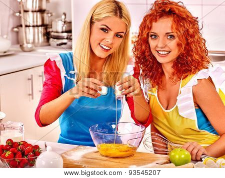 Young women  baking cookies in oven together.