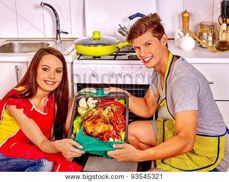 Happy couple cooking chicken at kitchen. Woman in red apron.