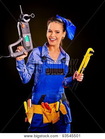 Happy woman builder with construction tools on black background.