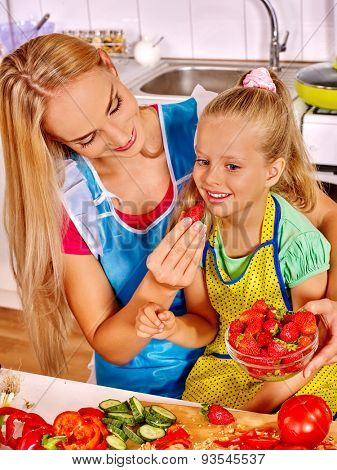 Happy mother feed little girl kid at kitchen.