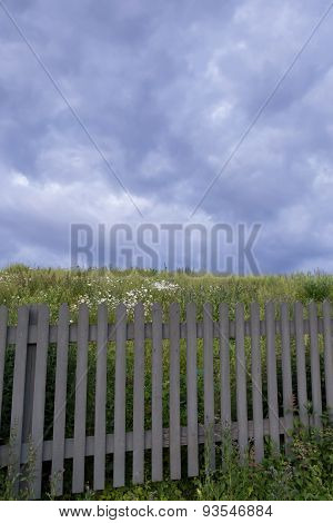 A Greyish Fence With A Stormy Sky