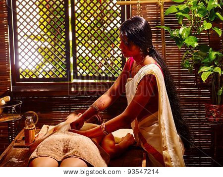 Young woman having oil Ayurveda spa treatment. Day of window.