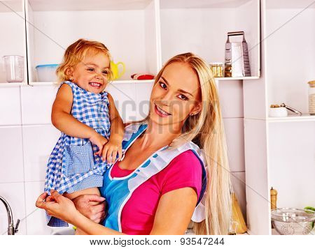 Mother  feed happy child on hand at kitchen .