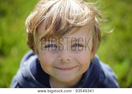 Happy grimy kid against green blurred natural background