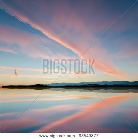 Beautiful sunset over sea with mountains on the horizon