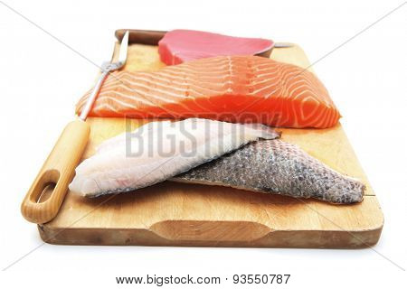 raw set of sea fish food : salmon , red tuna, and sole fish chunks served on wooden plate isolated on white background