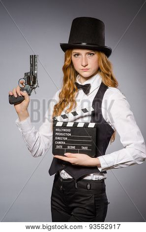 Pretty girl wearing retro hat  and holding clapperboard isolated on gray