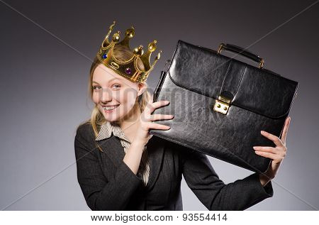 Pretty businessman with crown and case isolated on gray