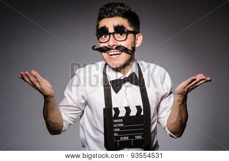 Young man with false moustache holding clapperboard isolated on gray
