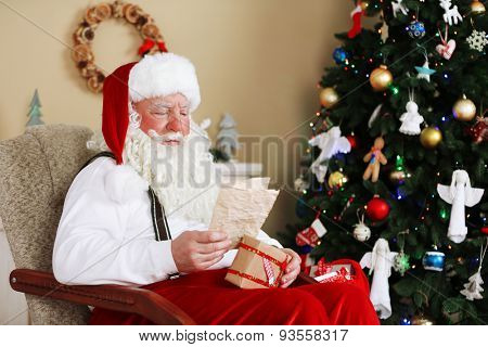 Santa Claus sitting with children letters in comfortable chair near fireplace at home