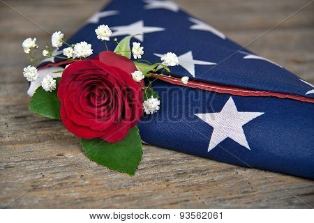 rose in folded American flag