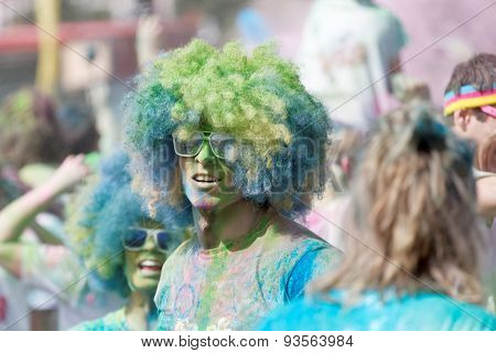 Two Partpicients Wearing Large Wigs And Covered With Blue And Green Color Powder