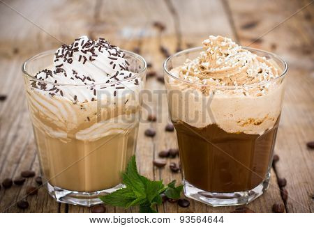Two glasses of ice coffee with milk and whipped cream
