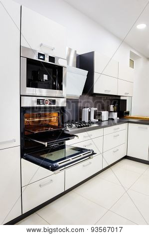 Modern luxury hi-tek black and white kitchen, clean interior design, focu at oven with door open