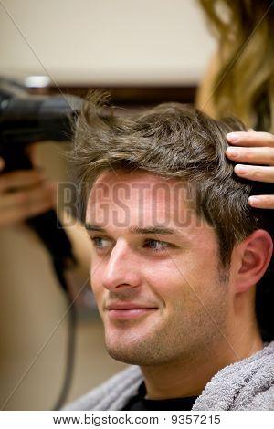 Peluquería femenina, seque el cabello de su cliente masculino