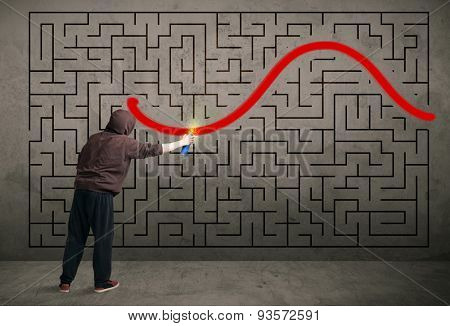 Young urban painter drawing a red solution line on the wall maze