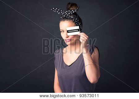 Pretty girl with censored paper sign holding in hand