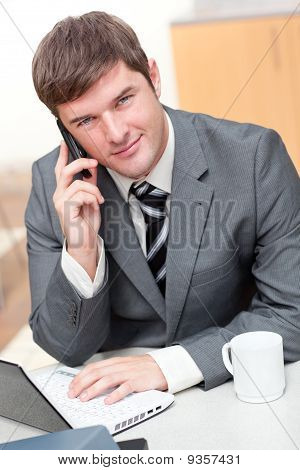 Confident Businessman Talking On Phone And Using His Laptop