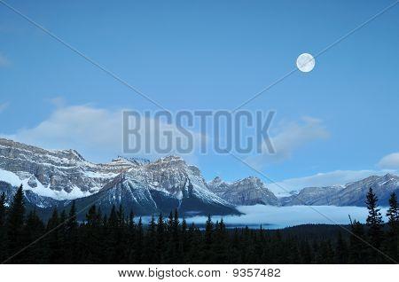 Conjunto de lua cheia durante montanhas rochosas canadenses