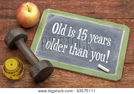 Old is 15 years older than you  -  slate blackboard sign against weathered red painted barn wood with a dumbbell, apple and tape measure