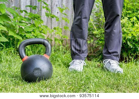 fitness workout with a heavy iron competition kettlebell (62lb/28 kg) on green grass in backyard - outdoor training concept