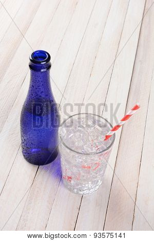 HIgh angle shot of a glass full of water and ice and red and white drinking straw next to a blue bottle. Vertical format with copy space on a rustic wood surface.